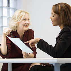Two Ladies Using Their Corporate Minute Taking Training